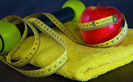 Fitness theme: red apple with measuring tape on a yellow towel.