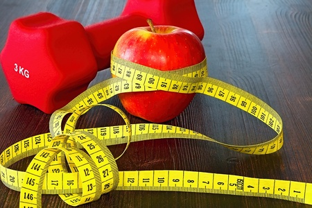 Fitness center with an apple for snack after exercise, a dumbbell and a metro for checking body parameters. Imagens