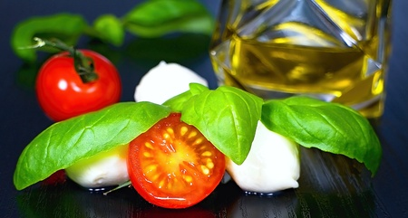 Ingredients for the preparation of Caprese Mediterranean salad: tomatos, mozzarella, basil leaves and olive oil.