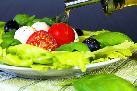 Olive oil is an important part of refreshing summer salads: Salad Caprese, a traditional and Mediterranean salad.
