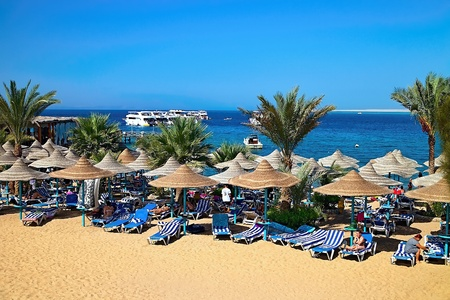 Sunny beach in Egypt with a Red Sea background and a floating boat. Imagens