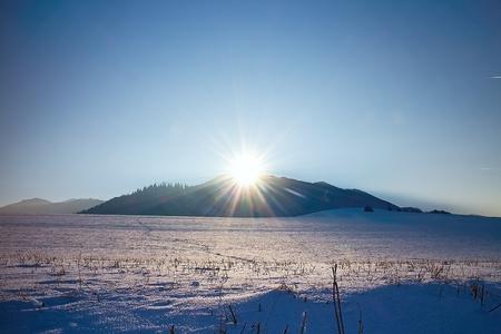 Winter sun rays over snowy meadow in Liptov. Poludnica in the background. Imagens