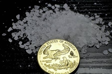 Concept: salt and gold. Gold coin American Eagle 1 ounce compared to salt as a value of life. Gold coin, coarse salt arranged on a table. Imagens - 150421049