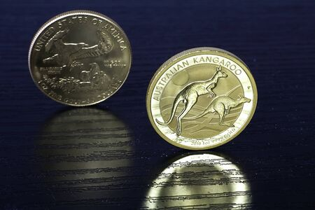 Golden Age: 1 ounce Kangaroo Australian gold coin and American Eagle gold coin in the background. Coins on the black table. Imagens
