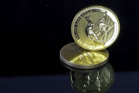 Australian Kangaroo gold coin built on 1 ounce gold coin American Eagle. Gold, mirroring and table.
