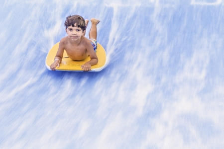 shorebreak: Small child riding a wave on a boogie board