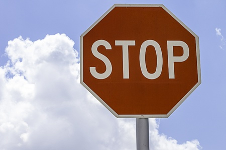 Close shot of a stop sign surrounded by blue sky and clouds
