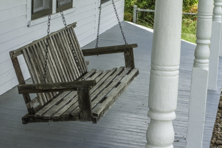 Old wooden porch swing hanging on a front porch of an old home