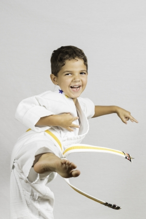 A young boy jumping and kicking dressed in a karate uniform
