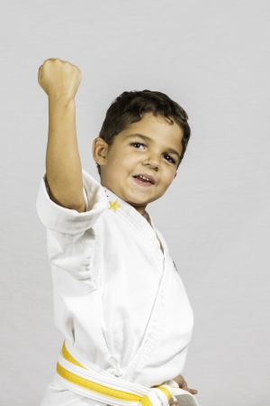 A young boy punching up dressed in a karate uniform  photo