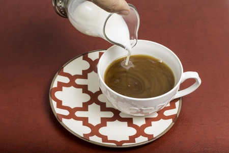 creamer: A coffee mug that has creamer being poured in.