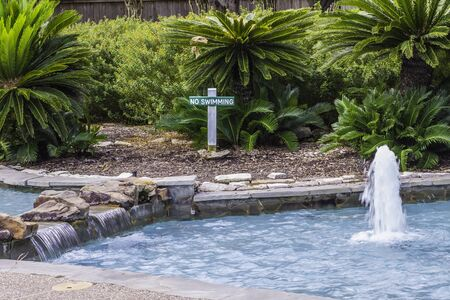 no swimming sign: A small waterfall and fountain sitting in front of a No Swimming sign.