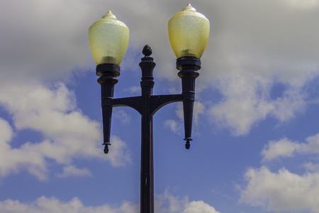 A vintage lamp post in an old park with a blue sky in the background.