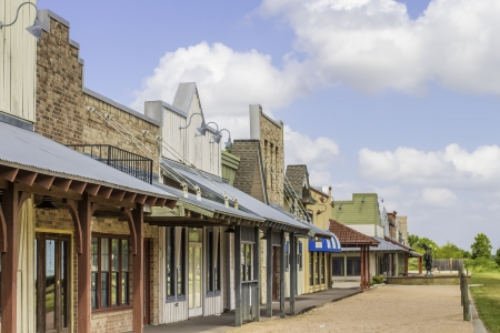 A row of old western rural shops with a bright blue sky in the background. Archivio Fotografico