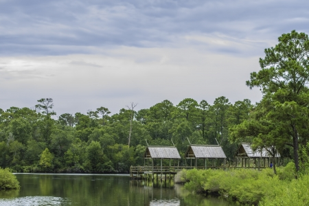 Small fishing piers among a calm lake with trees draped behind them. photo