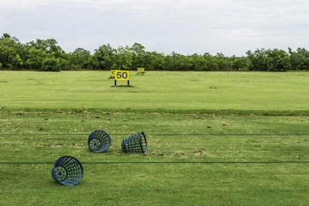 A driving range shot showing yardage signs and empty golf ball baskets.