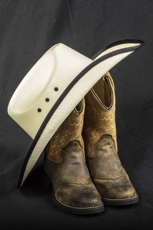 black cowgirl: A close shot of a pair of boots and a cowboy hat.