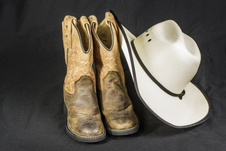 cowgirl boots: A close shot of a pair of boots and a cowboy hat.