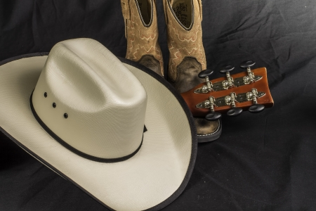 black cowgirl: A close shot of a pair of boots. cowboy hat and a guitar handle.