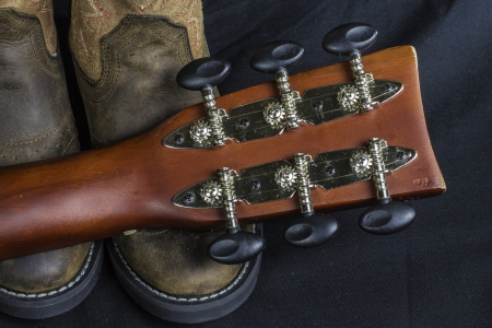 cowgirl boots: A close shot of a pair of boots and a cowboy guitar handle. Stock Photo
