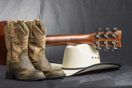 brown leather hat: A close shot of a pair of boots. cowboy hat and a guitar handle.