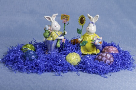 A group of easter eggs surrounded by fake blue grass and two rabbit statues.