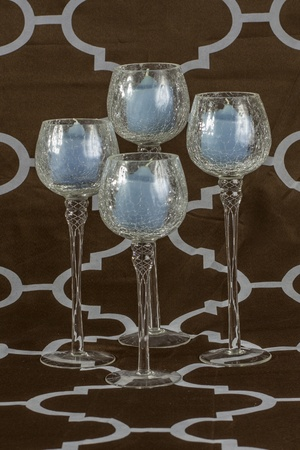 Glass tea light candle holders arranged together with a brown background.
