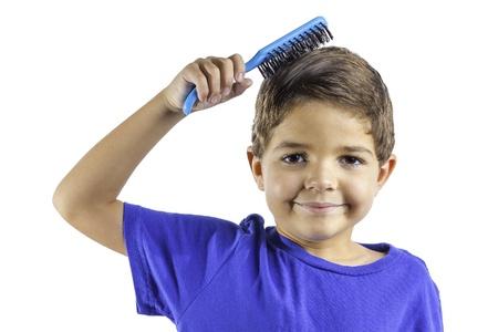 Un ragazzo giovane spazzolare i capelli isolato su uno sfondo bianco. Archivio Fotografico