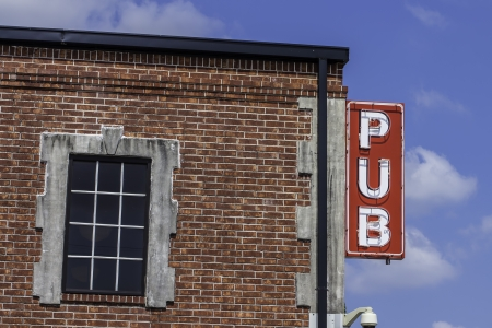 A pub sign located on the side of a brick building. photo