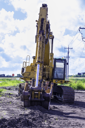 sand quarry: A large yellow excavator digging through the soil. Stock Photo