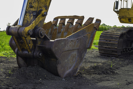 sand quarry: An excavator bucket sitting on the fresh dug soil.