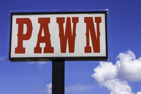 shop sign: A large roadside sign for a pawn shop.