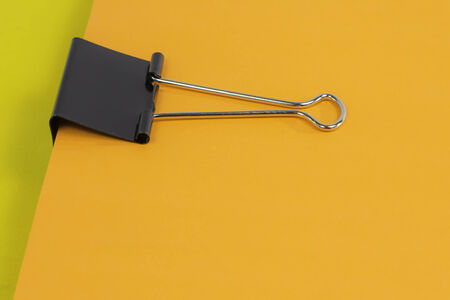 binder clip: A black binder clip holding together a stack of colorful paper. Stock Photo
