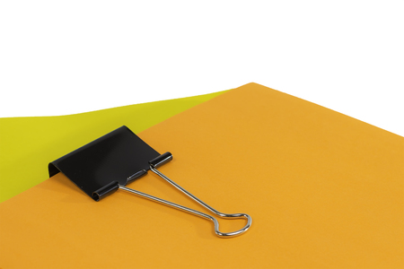 A black binder clip holding together a stack of colorful paper. Фото со стока - 22797900