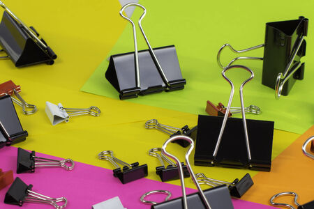 A scattered group of binder clips laying on colorful paper. Archivio Fotografico