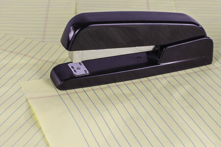 legal pad: A black stapler sitting on top of yellow legal pad sheets. Stock Photo