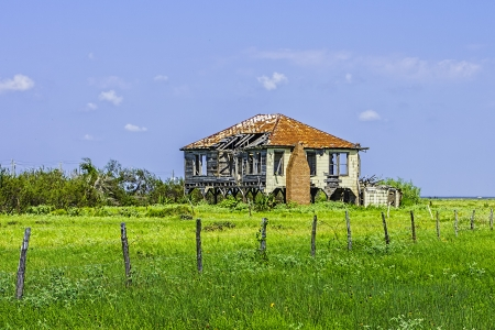 An old abandoned home that is severely weathered and falling apart.