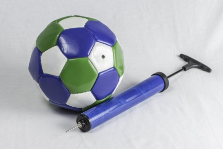 A soccer ball and air pump isolated on a white .