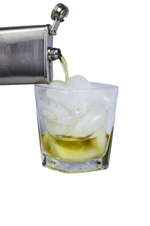 A hip flask pouring liquor into a glass of ice.