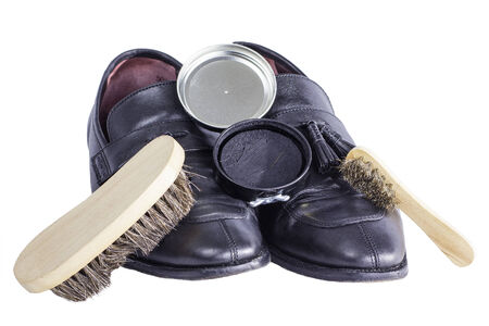 A pair of black dress shoes mixed with shine brushes and polish.