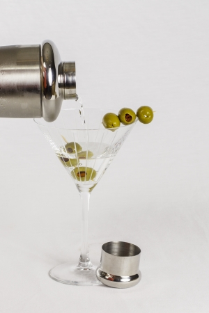 martini shaker: A martini glass filled with olives getting a cocktail poured from a shaker.