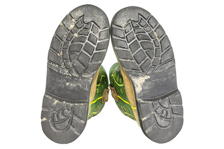 tread: The bottom black soles of a pair of work boots isolated on a white.