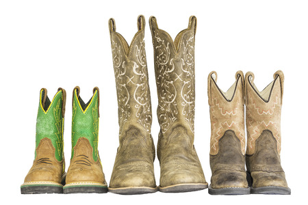 cowboy boots: A row of three pairs of cowboy western boots isolated on a white.