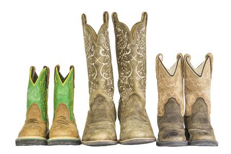 botas: Una fila de tres pares de botas de vaquero occidentales aislado en un blanco.