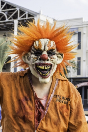 An evil scary clown costume wearing an orange jumpsuit