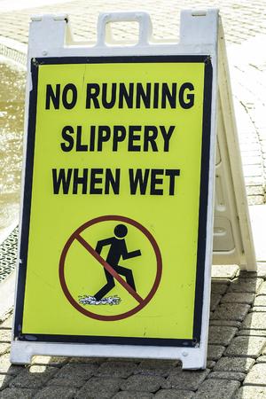 no correr: Un pueblo de advertencia signo no correr porque el suelo se resbaladizo cuando est� mojado Foto de archivo