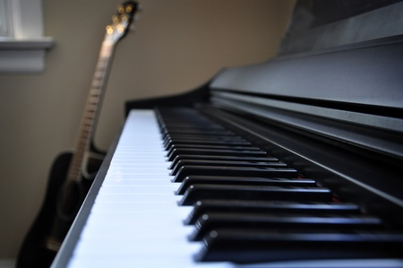 keyboard: Side view of a piano keyboard with an acoustic guitar in the background