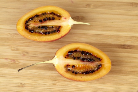 tamarillo: Tamarillo halved on a wooden board