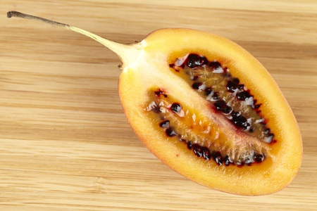 tamarillo: Halved tamarillo  tree tomato  on a wooden board Stock Photo