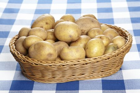 Basket with potatoes on checkered tablecloth